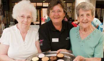 Two guests and one member of staff holding a tray of cupcakes at Revitalise centre