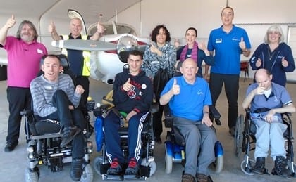 Group of guests in wheelchair and carers on accessible flying excursion