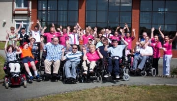 Group of disabled guests and carers cheering outside Revitalise Sandpipers