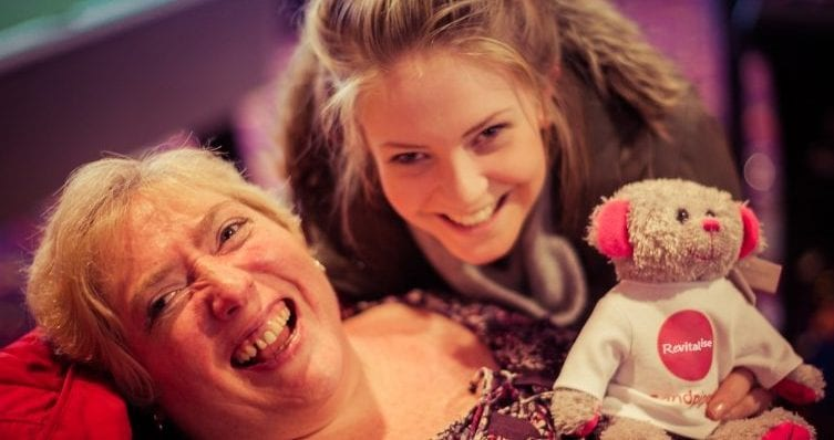 Happy guest holding a Revitalise teddy bear next to carer