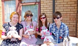 Group of volunteers outside holding Revitalise teddy bears