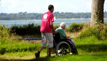 Carer pushing guest in wheelchair in the garden at Netley Waterside House
