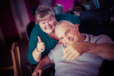 Guest and carer with thumbs up at Revitalise centre