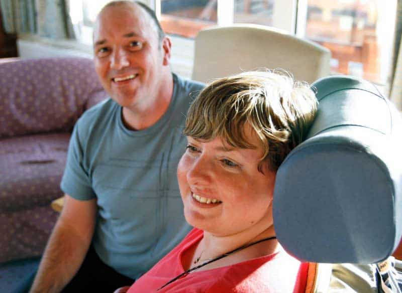 disabled guest and carer smiling