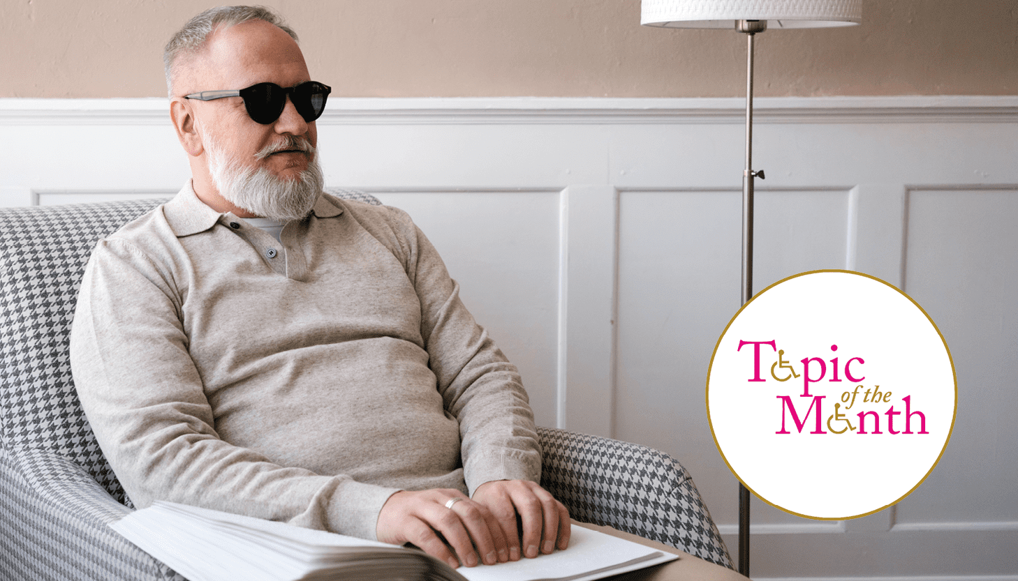 Blind man sitting in armchair reading with logo overlay saying Topic of Month