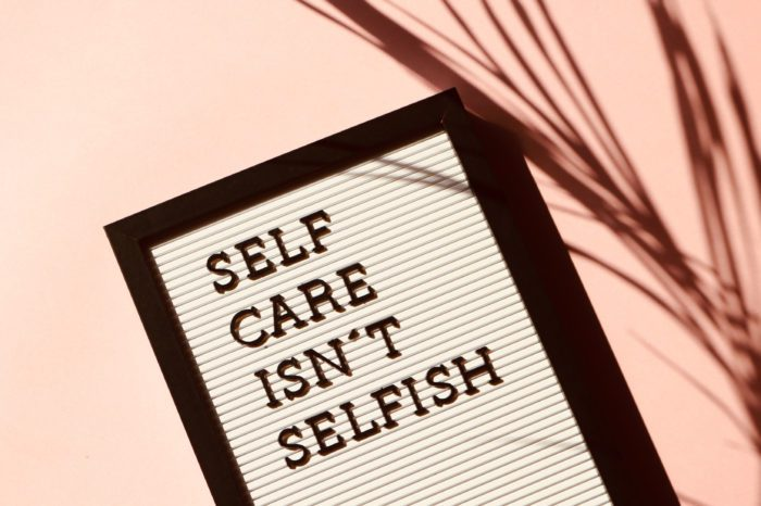 Sign that says Self Care Isn't Selfish against pink background
